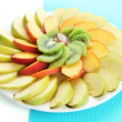 Stock Photo: Assortment of sliced fruits on plate, isolated on white