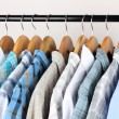 Shirts with ties on wooden hangers on light background — Stok fotoğraf