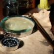 Old paper with ink pen and magnifying glass near lighting candle on wooden table — Stok fotoğraf