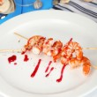 Grilled shrimp with sauce on plate on wooden table close-up — Stock Photo