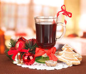 Hot tasty drink with christmas candy and other decorations on bright background — Stock Photo