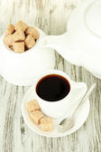 Cup of coffee, teapot and sugar-bowl on color wooden background — Stock Photo