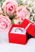 Roses and a ring on a white cloth — Stock Photo