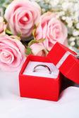 Un anello su un panno bianco e rose — Foto Stock