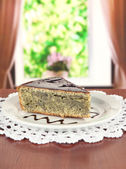 Delicious poppy seed cake on table in room — Stock Photo