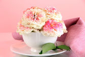 Roses in cup on napkins on pink background — Stock Photo