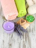 Bodegón con lavanda vela, jabón, bolas de masaje, jabón y lavanda fresca, sobre fondo de madera — Foto de Stock