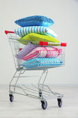Shopping cart with pillows, on gray background — Stock Photo