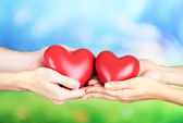 Hearts in hands on nature background — Stock Photo