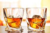 Glasses of whiskey, on bright background — Stock Photo