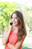Beautiful young woman speaking on mobile phone at summer park — Zdjęcie stockowe
