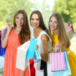 Three beautiful young woman with shopping bags in park — Stock Photo #29860031