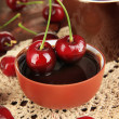 Ripe red cherry berries in cup and chocolate sauce on wooden table close-up — Stock Photo