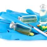 Medical bottles gloves and syringe isolated on white — Stock Photo #29860809