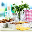 Stock Photo: Food in boxes of foil on tablecloth on window background