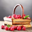 Ripe sweet raspberries in basket on wooden table, on grey background — Stock Photo