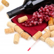 Stock Photo: Bottle of wine, grapes and corks, isolated on white