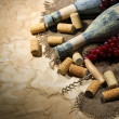 Old bottles of wine, grapes and corks on old paper background — Stock Photo