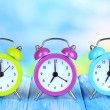 Colorful alarm clocks on table on blue background — Stock Photo #29861263