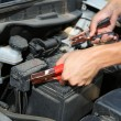 Stock Photo: Car mechanic uses battery jumper cables to charge dead battery