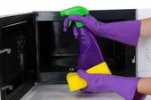 Ręka z gąbki do czyszczenia kuchenka mikrofalowa, na białym tle — Zdjęcie stockowe