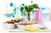 Food in boxes of foil on tablecloth on window background — Stock Photo