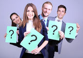 Business team standing in row with question mark on grey background — Stockfoto