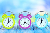 Colorido reloj despertador de mesa sobre fondo azul — Foto de Stock