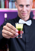 Portrait of handsome barman with short cocktail, at bar — Stock Photo