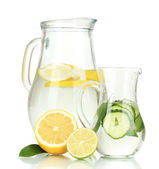 Cold water with lemon, cucumber and ice in pitchers isolated on white — Stock Photo