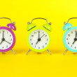 Colorful alarm clock on yellow background — Stock Photo