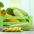 Stock Photo: Sliced and whole raw zucchini in wooden crate, outdoors