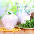 Stock Photo: Fresh dairy products with greens on wooden table on natural background