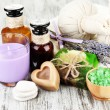 Stock Photo: Still life with lavender candle, soap, massage balls, bottles, soap and fresh lavender, on wooden background