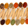 Assortment of spices in wooden spoons, isolated on white — Stock Photo #29907897