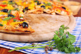 Tasty pizza with kitchen herbs on wooden table close-up — Stock Photo