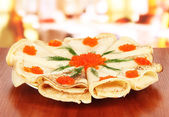 Delicious pancakes with red caviar on table in cafe — Stock Photo
