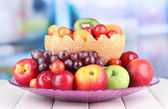 Assortment of juicy fruits on wooden table, on bright background — Photo