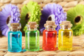 Bottles with colored liquids on wicker wooden background — Stock Photo
