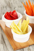 Bright fresh vegetables cut up slices in bowls on wooden table close-up — Stock Photo