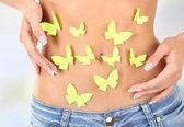Butterfly on stomach on light background — Stock Photo