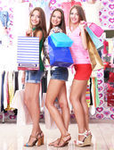 Three beautiful young woman in shop with shopping bags — Foto de Stock