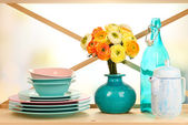Beautiful dishes on wooden cabinet on bright background — Stock Photo