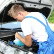 Man pours liquid for washing glasses to car — Stock Photo #29993437