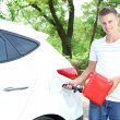Man pouring fuel into gas tank of his car from red gas canister — Stock Photo #29993443
