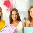 Stock Photo: Three beautiful young woman in shop with shopping bags
