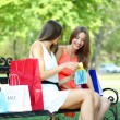Stock Photo: Two beautiful young woman with shopping bags in park