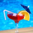 Tasty cocktail on swimming pool background — Stock Photo #29993495