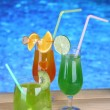 Tasty cocktails on swimming pool background — Stock Photo #29993507
