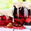 Stock Photo: Home made berry jam on wooden table on bright background